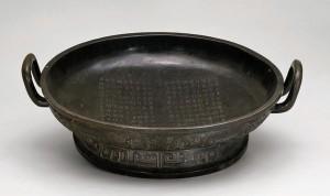 Бронзовый сосуд с двумя рядами символов в центре, описывающих поколения семьи Вэй на одной половине, а на другой половине список семи правителей Чжоу. Конец X в. до н.э.